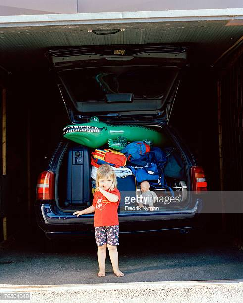 A girl in front of a crammed car.