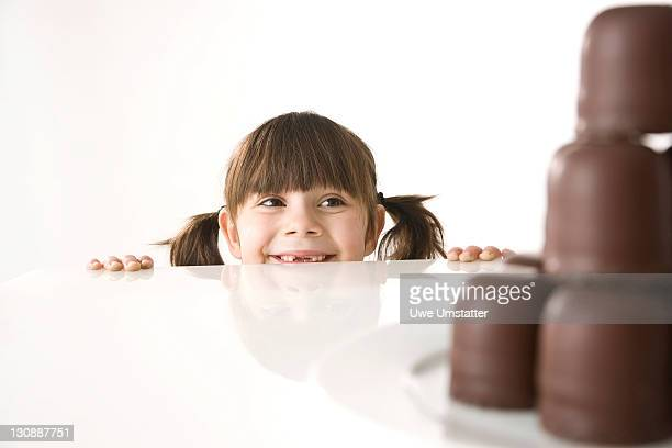 Girl in front of a plate of chocolate marshmallows