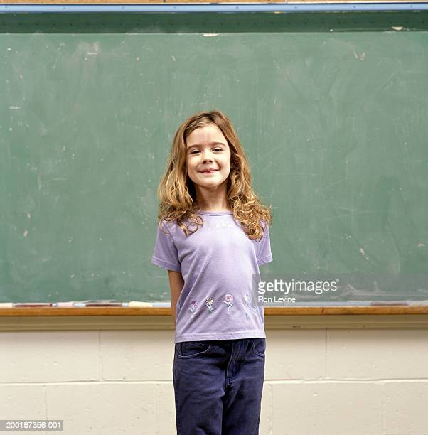girl (9-11) in front of blackboard, portrait - schulkind stock-fotos und bilder