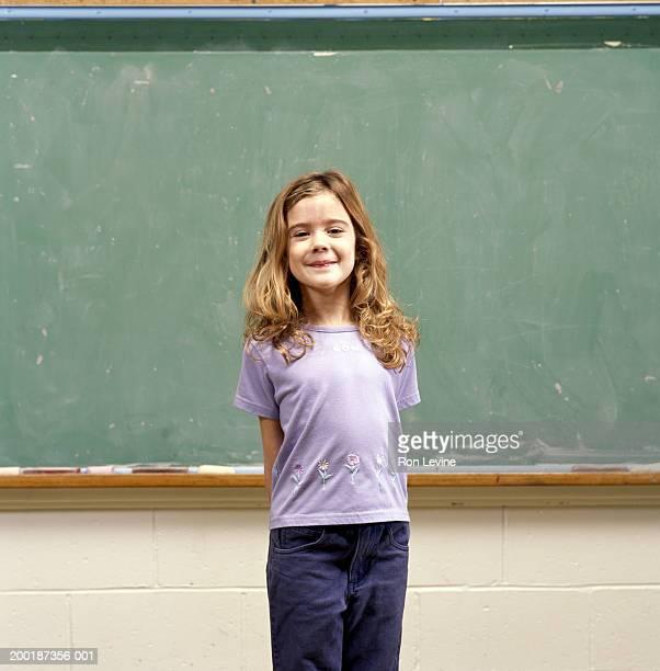 girl (9-11) in front of blackboard, portrait - 10 11 años fotografías e imágenes de stock