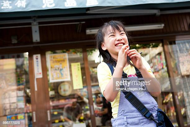 Girl in front of Dagashi-ya eating candy