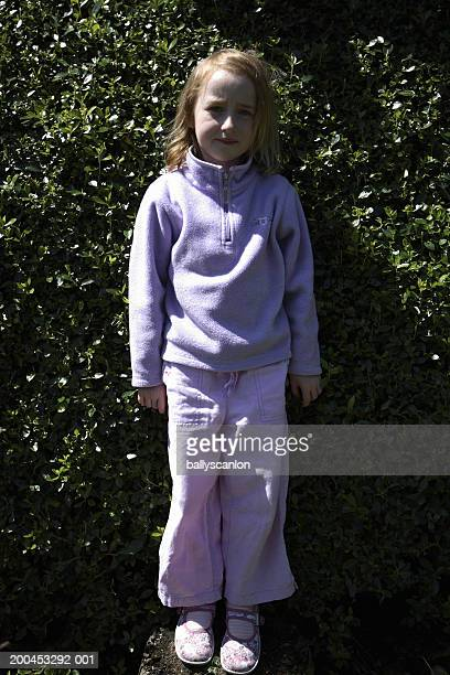 Girl (5-7) in front of hedge, portrait