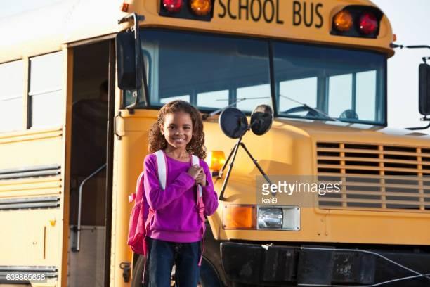 Girl in front of school bus