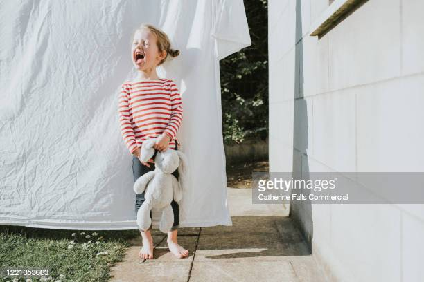 girl in front of washing line - teddy bear stock pictures, royalty-free photos & images