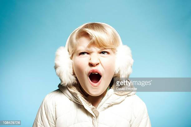 Girl in fur ear muffs in front of blue background