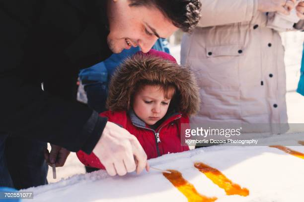 girl in fur hood with father making lolly in snow ice - 毛皮の飾り ストックフォトと画像