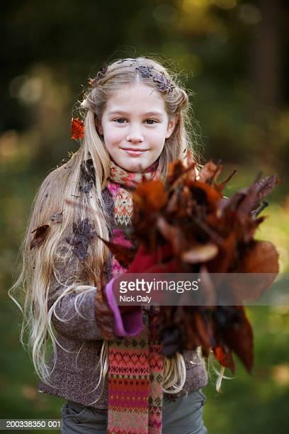 girl (7-9) in garden holding dead leaves, portrait - dead girl imagens e fotografias de stock