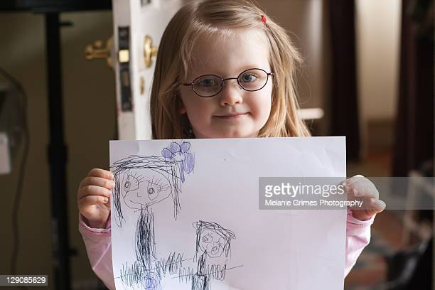 Girl in glasses holds up picture