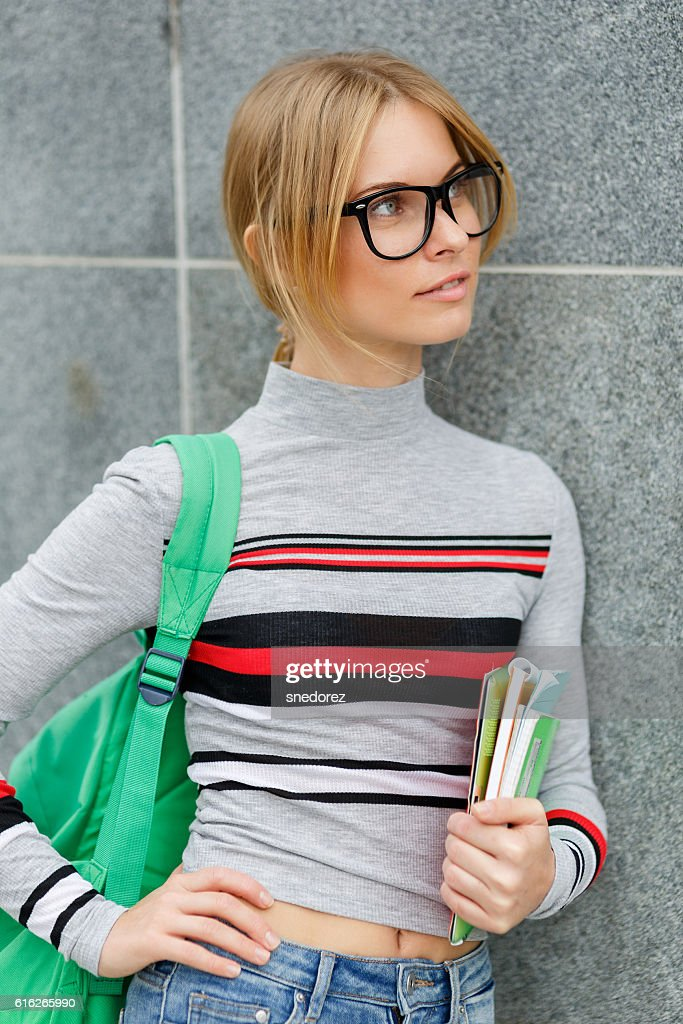 Girl in glasses with backpack at gray wall : Stock Photo