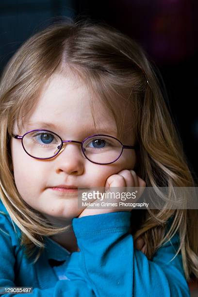 Girl in glasses with hand on her chin