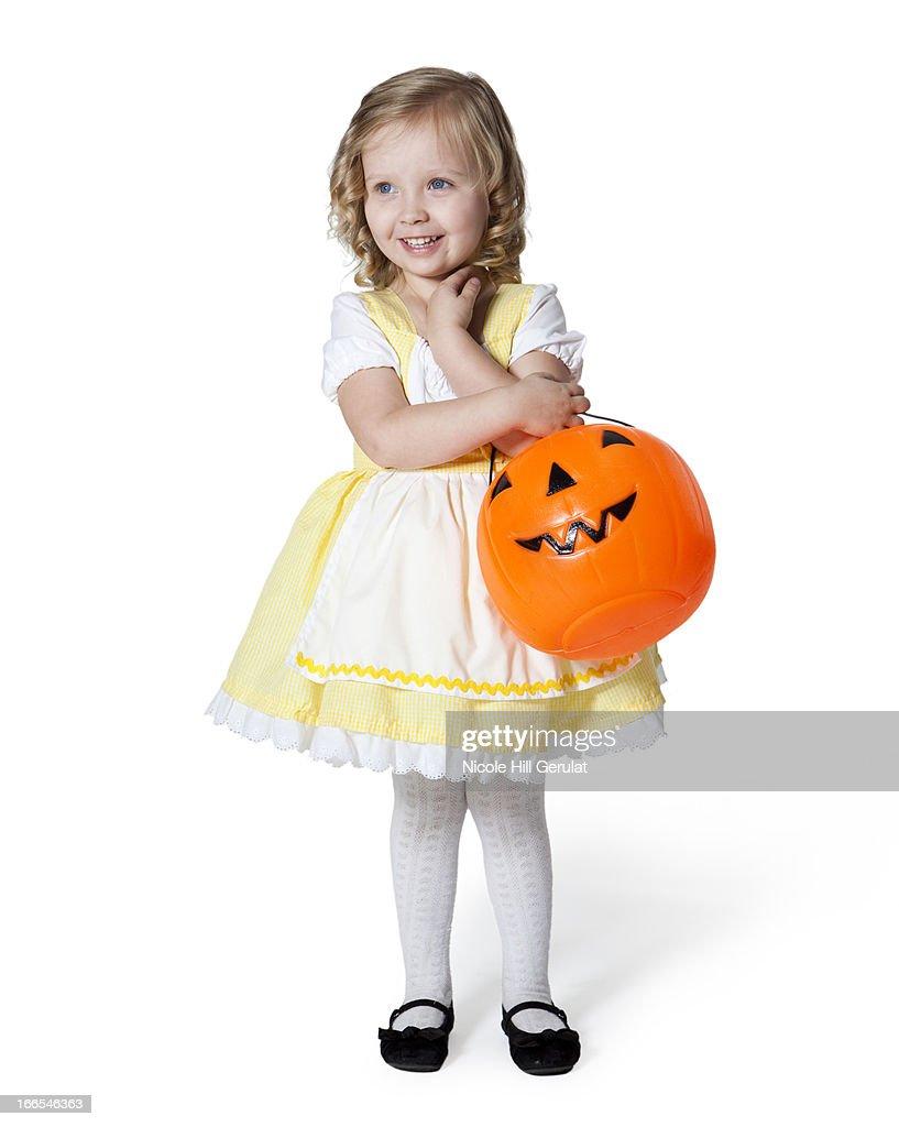 Girl (2-3) in Goldilocks costume with pumpkin lantern for Halloween : Stock Photo