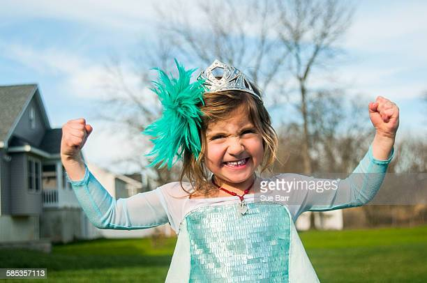 Girl in gown with feather fascinator playing outdoors