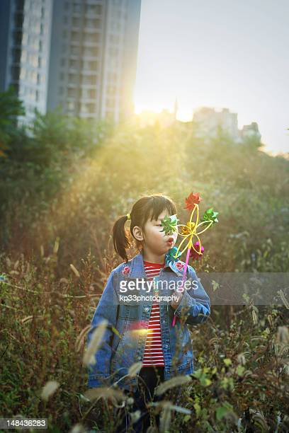 Girl in grass with windmill