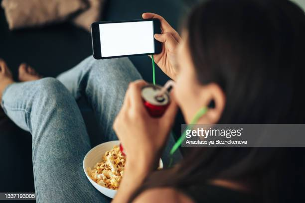 girl in green headphones looks into smartphone and drinks juice through straw from can - international match stock pictures, royalty-free photos & images