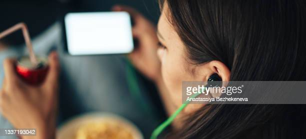 girl in green headphones looks into smartphone with can of juice and popcorn - international match stock pictures, royalty-free photos & images