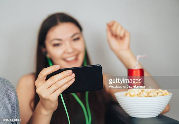 girl in green headphones watches the game and cheers for her team - international match stock pictures, royalty-free photos & images