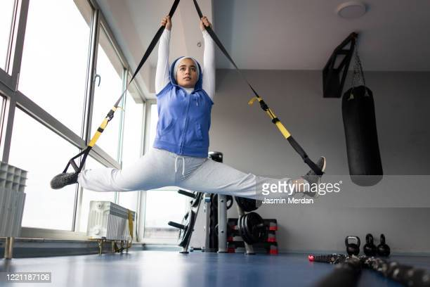 girl in gym stretching legs doing the split - frau gespreizte beine stock-fotos und bilder