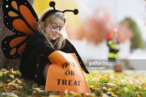 Girl in Halloween costume with bag of candy