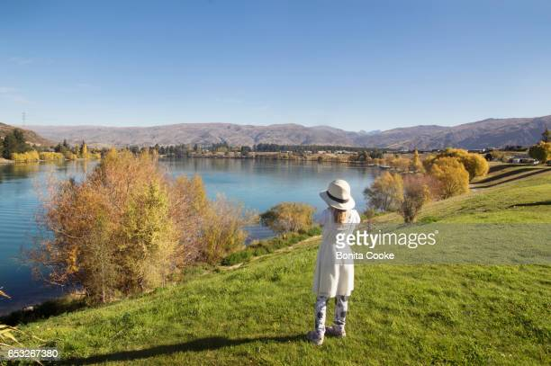 Girl in hat and dress, looking at Lake Dunstan, in Cromwell, Central Otago