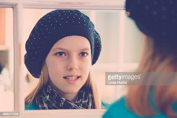 Girl in hat and scarf looking at self in mirror