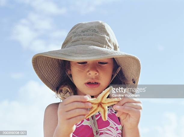 girl (4-6) in hat holding starfish, low angle view - invertebrate stock photos and pictures