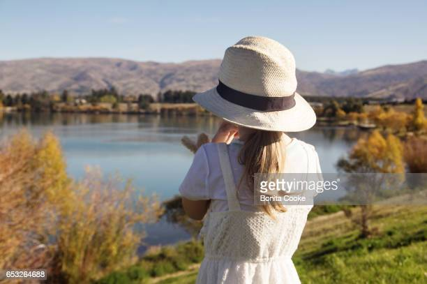 Girl in hat, looking at Lake Dunstan, in Cromwell, Central Otago