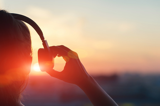 Girl in headphones listening to music in the city at sunset 958364166