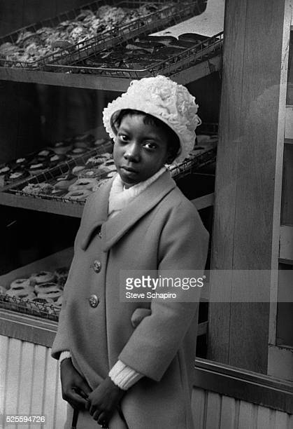Girl in her Easter finery stands in front of a bakery window