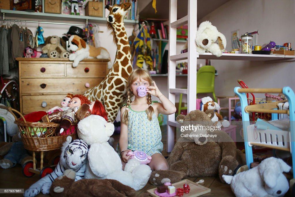 A girl in her filled bedroom : Stock Photo