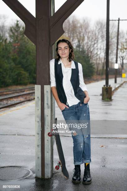 Girl in her late teens at a train station on a rainy afternoon with her skateboard, portrait.