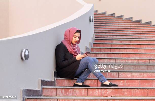 a girl in hijab (head scarf) busy in using cell phone while sitting on stairs outdoor. - pakistan girl stock photos and pictures