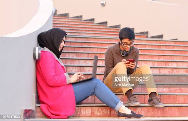 a girl in hijab (head scarf) busy in using laptop and a young boy using cell phone beside her sitting on stairs outdoor. - punjabi girls images stock photos and pictures