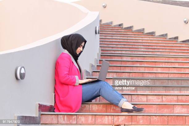 a girl in hijab (head scarf) busy in using laptop while sitting on stairs outdoor. - punjabi girls images stock photos and pictures