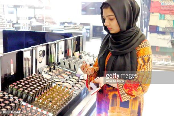 a girl in hijab (veil) buying lipsticks - modest clothing stock pictures, royalty-free photos & images