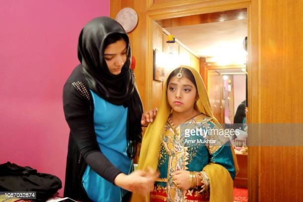girl in hijab (veil) helping a young girl to wear traditional asian (pakistani and indian) bride dress and jewelry - punjab pakistan stock pictures, royalty-free photos & images
