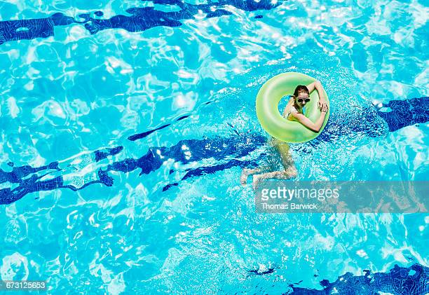 Girl in inflatable ring floating in outdoor pool