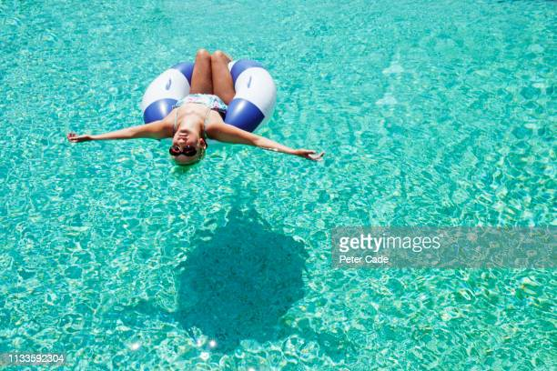 girl in inflatable toy in pool - bronzage humour photos et images de collection