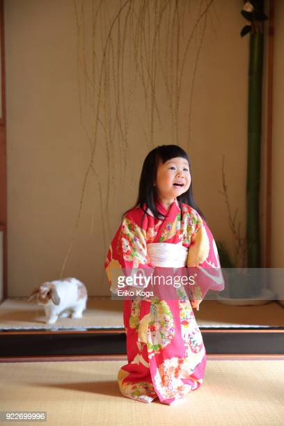 Girl in kimono playing with rabbit