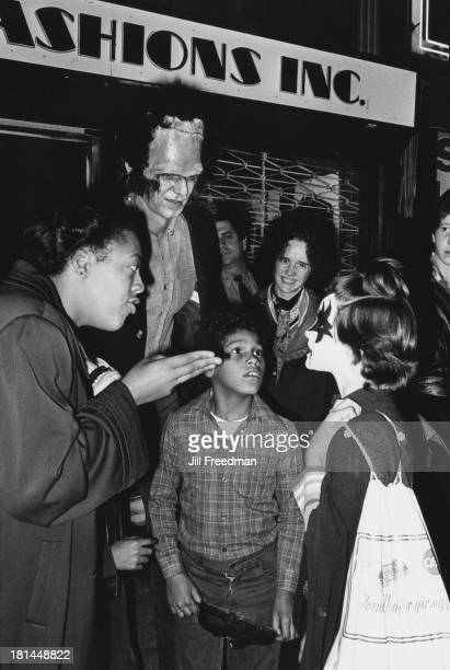 A girl in 'Kiss' make up talks to adults on the Lower East Side during the Halloween celebrations New York City circa 1978