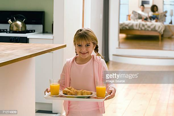 Girl in kitchen carrying breakfast on tray