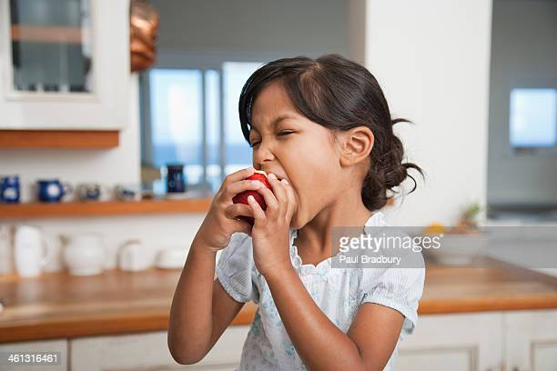 Girl in kitchen eating red apple