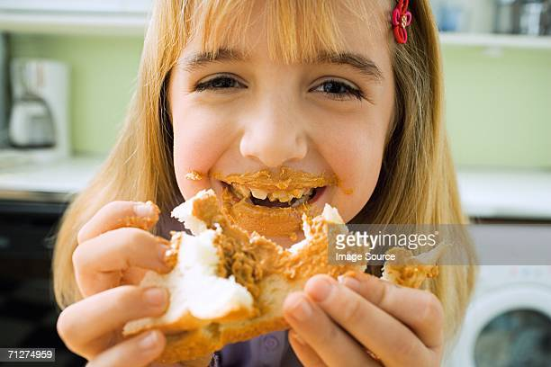Girl in kitchen messily eating sandwich