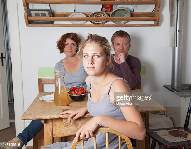 Girl in kitchen, parents in background