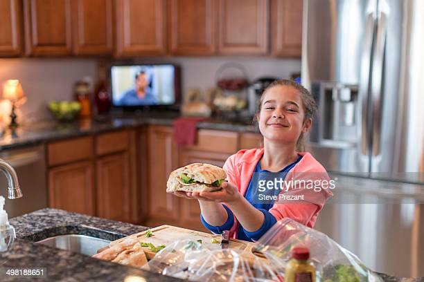 Girl in kitchen preparing sandwich