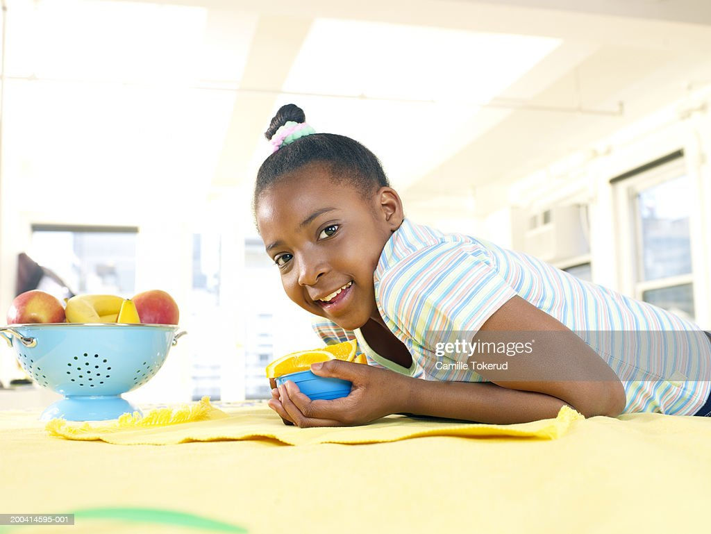 Girl (9-11) in kitchen with bowl of orange sections, portrait : Stock Photo