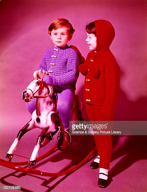 Girl in knitted outfit stands next to boy on rocking horse Photographic Advertising Limited founded in 1926 created multipurpose stock images with...
