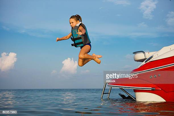 Girl in lifejacket jumping off boat, Florida, United States