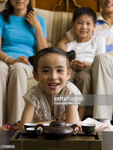 Girl in living room with tea pot and cups with parents and brother in background