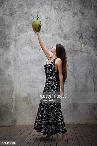 Girl in long dress holding and looking at coconut
