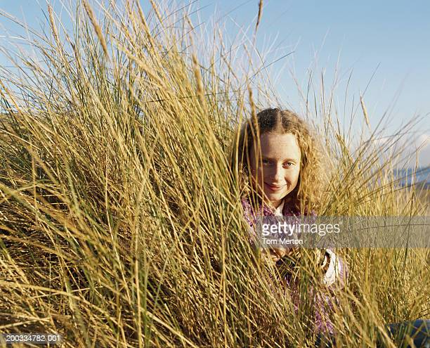 girl (12-14) in long grass on beach, smiling, portrait - camber sands stock photos and pictures